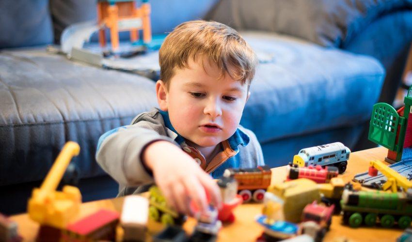 Dečak koji se igra sa igračkama na stolu