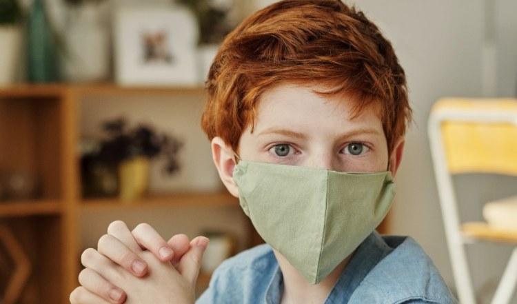 Dečak koji nosi zaštitnu masku zelene boje na licu