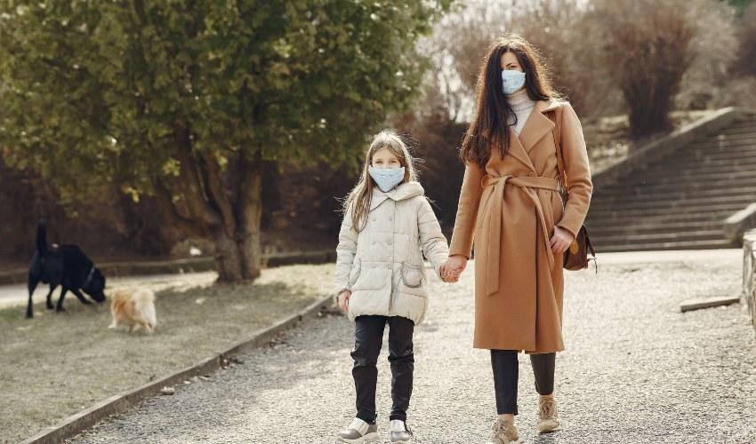 Majka i ćerka šetaju sa zaštitnim maskama na licu