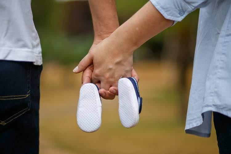 muškarac i žena drže u ruci obuću za bebu