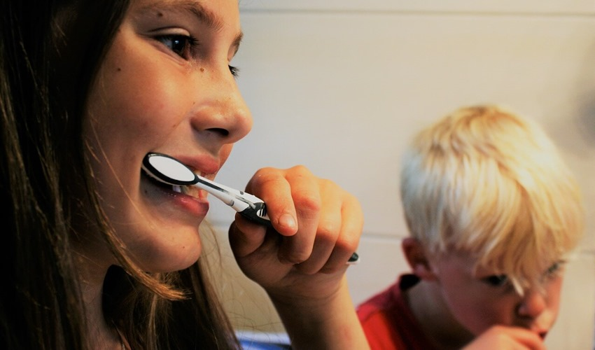 Devojčica i dečak peru zube