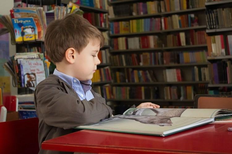Dečak koji čita knjigu u biblioteci