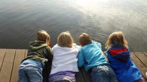 Deca leže na drvenom doku i gledaju i vodu