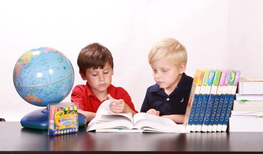 Dva dečaka koja sede za stolom i čiitaju knjigu