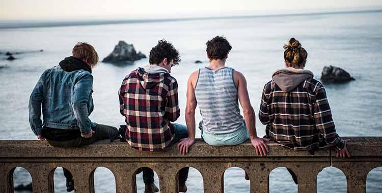 Tinejdžeri koji sede na ogradi i gledaju u more