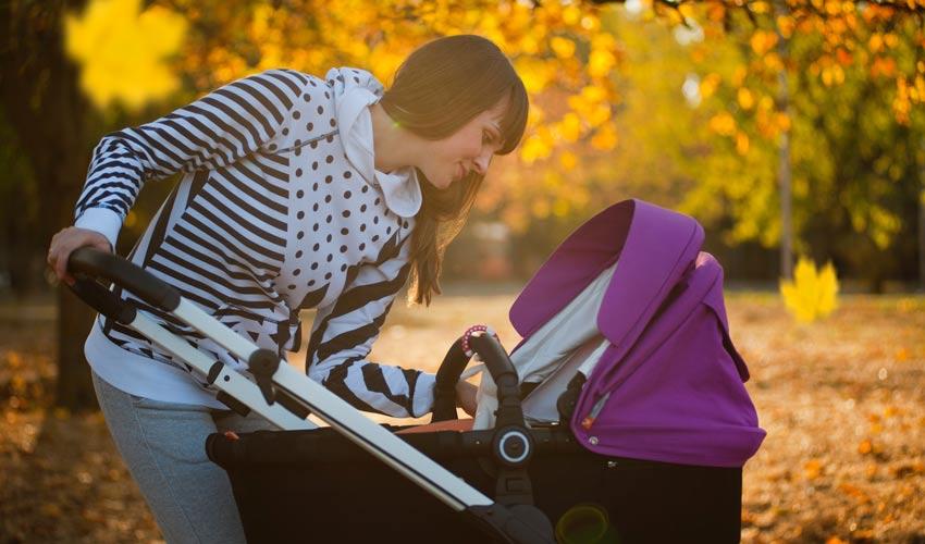 Mama pored kolica za bebe u parku