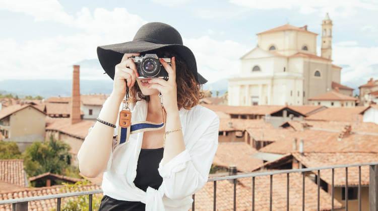 Devojka sa crnim šeširom i fotoaparatom na turističkoj destinaciji