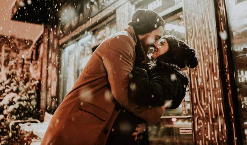 Devojka i dečko u zagrljaju se ljube dok veju pahulje