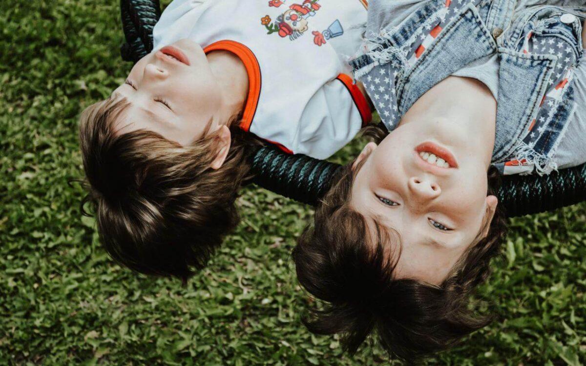 dva dečaka leže na travi