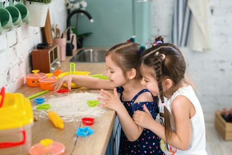 dve devojčice se igraju u kuhinji